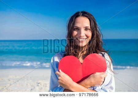 Smiling woman holding heart card at the beach on a sunny day