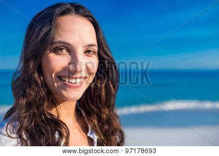 Smiling woman looking at camera at the beach on a sunny day