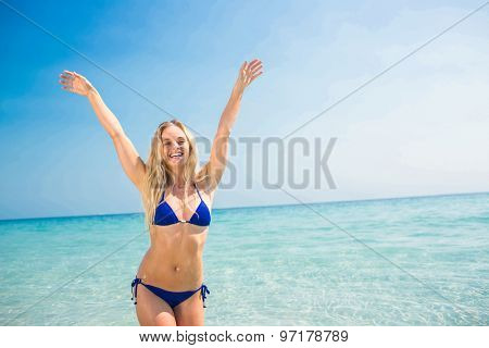 Smiling blonde woman walking into the ocean on a sunny day