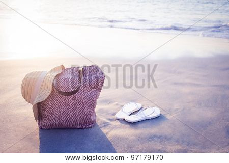 bag with sunhat and flip flop on the sand