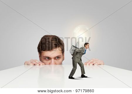 Young man looking from under table on man carrying bulb
