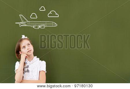 Cute girl of school age standing at blackboard
