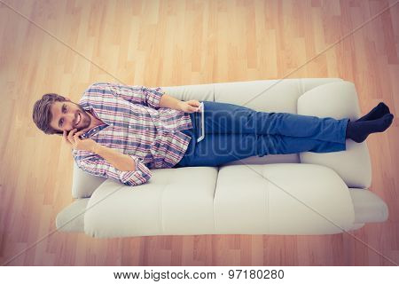 Portrait of a smiling businessman on the phone extended on the sofa