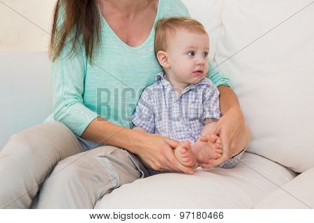 Happy mother with her baby boy at home in the living room