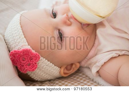 Beautiful cute baby girl drinking her baby bottle at home in bedroom