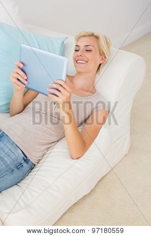Smiling blonde woman using her digital tablet in the sofa at home in the living room