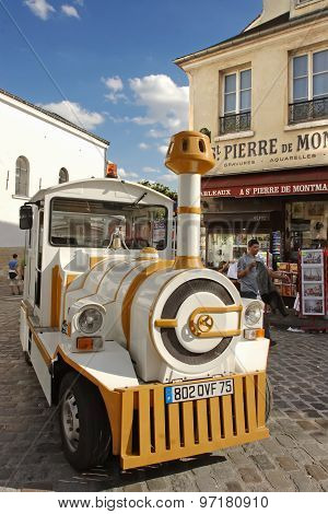 Paris, France, August 19, 2014. Small Train For Tourists Stops In Front Of Souvenir Stores. Montmart