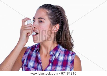 Pretty brunette woman using asthma inhaler on white background