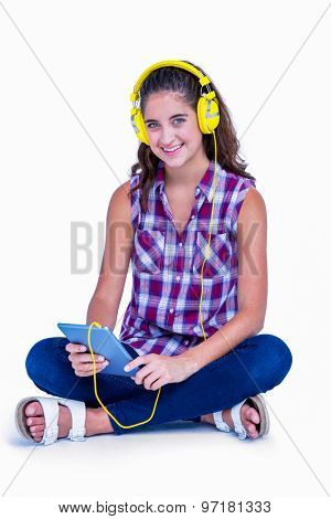 Pretty brunette listening music with her tablet computer on white background