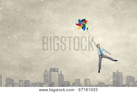 Young happy businessman flying in sky on colorful windmill