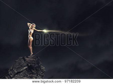 Young girl in white swim wear dancing in night