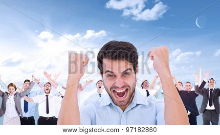 Cheering man looking at camera against blue sky
