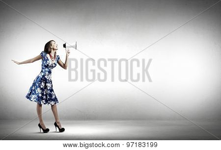Young woman making some announcement in trumpet