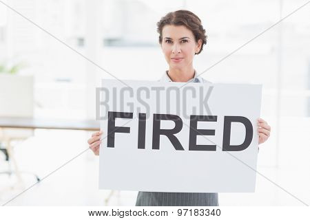 Businesswoman holding sign in front of her in an office