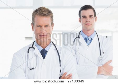 Unsmiling doctors looking at camera with arms crossed in medical office