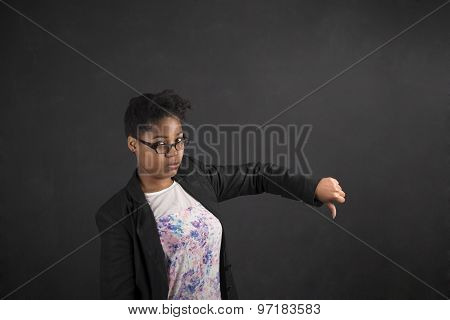 African Woman With Thumbs Down Hand Signal On Blackboard Background