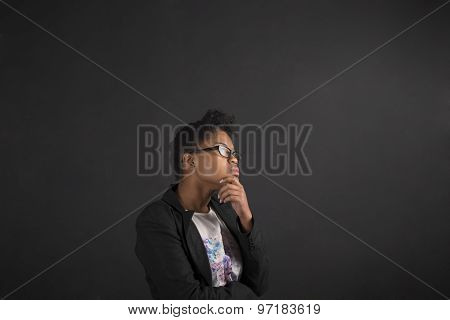 African Woman With Hand On Chin Thinking On Blackboard Background