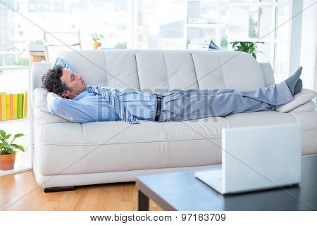 Businessman lying on couch in living room