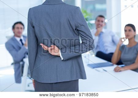 Businesswoman with fingers crossed behind her back in an office