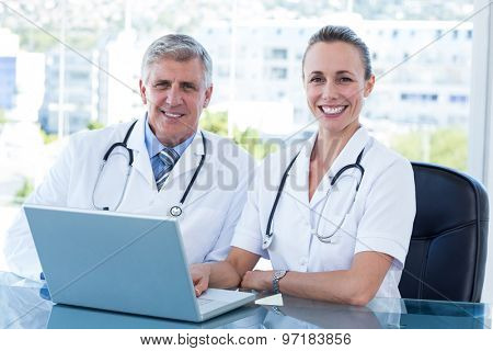 Smiling doctors working together on laptop in medical office