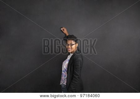 South African Or African American Woman Teacher Writing On Chalk Black Board Background