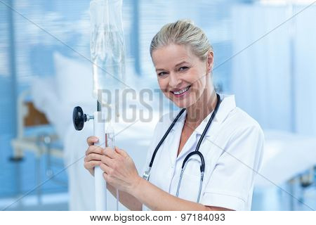 Nurse connecting an intravenous drip in hospital room