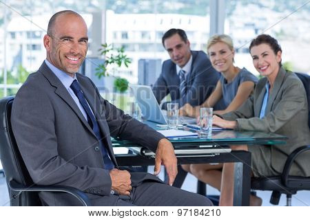 Businessman with his colleagues behind in the office