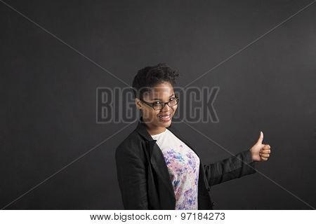 African Woman With Thumbs Up Hand Signal On Blackboard Background