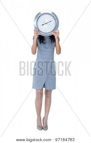 Businesswoman holding big clock in front of her face on white background