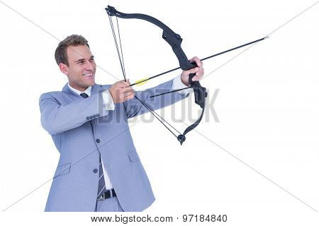 Happy businessman shooting with bow and arrow on white background