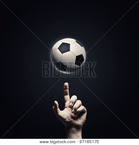 Close up of man hand pointing at soccer ball