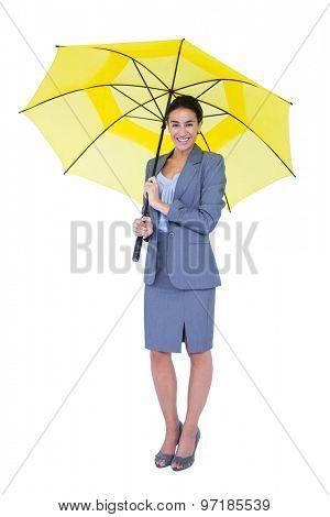 Smiling businesswoman sheltering under umbrella on white background