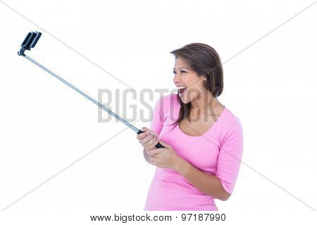 Pretty brunette using a selfie stick on white background