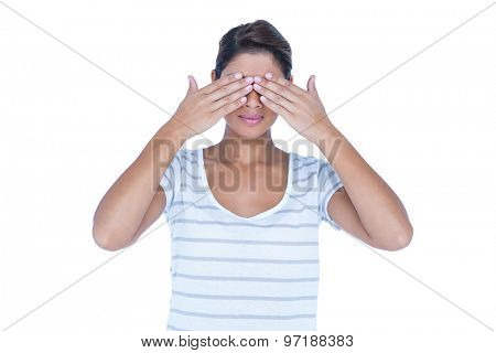 Pretty brunette hiding her eyes on white background