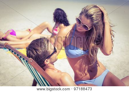 Happy couple relaxing on the deck chair at the beach