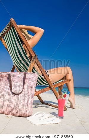 Side view of pretty brunette relaxing on deck chair at the beach on a sunny day