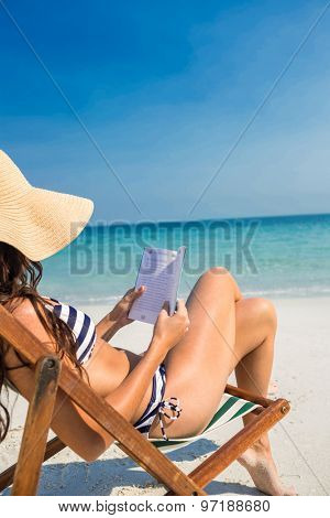 Pretty brunette reading on deck chair at the beach on a sunny day