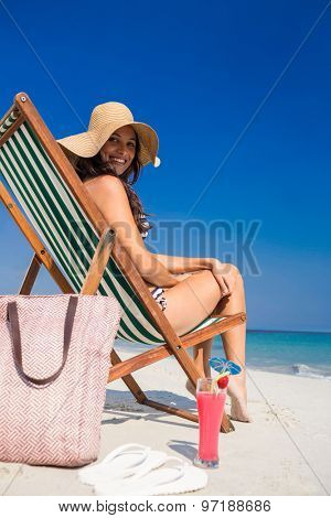 Pretty brunette looking at camera on deck chair on a sunny day