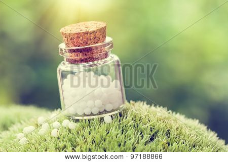 Bottle Of Homeopathy Globules On Green Moss. Retro Styled.