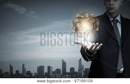 Close up of businessman hand showing gears mechanism