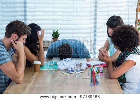 Exhausted creative business people in meeting at office