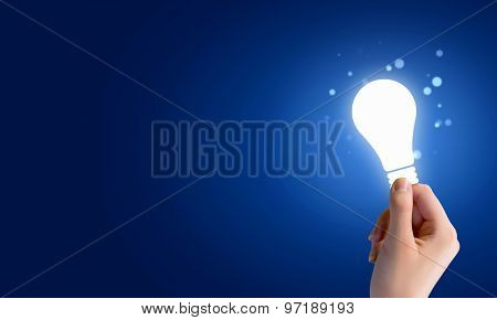 Close up of human hand holding light bulb