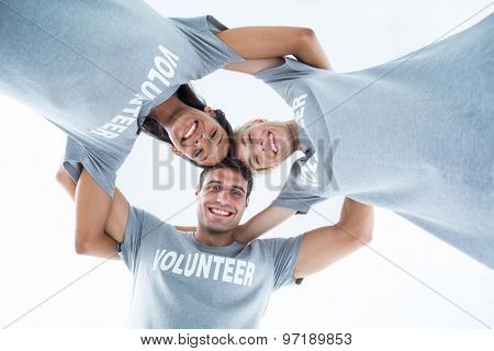 Low angle portrait of happy volunteers forming huddle