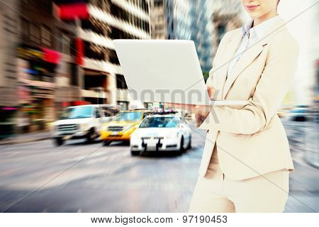 Confident businesswoman holding laptop against new york street
