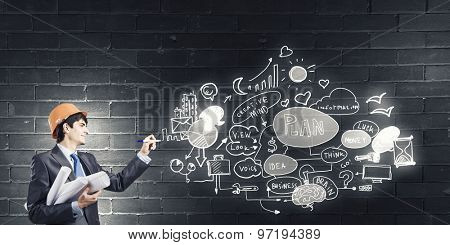 Young man engineer in helmet drawing business plan