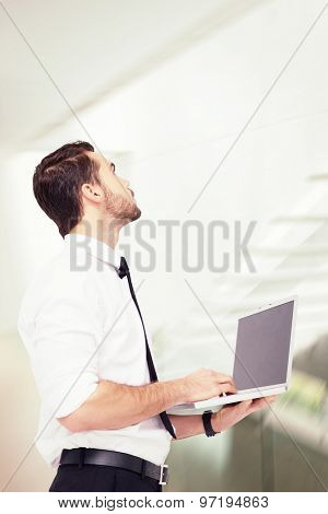 Sophisticated businessman standing using a laptop against stylish modern home interior with staircase