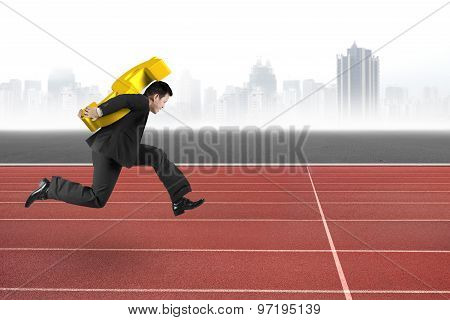 Businessman Carrying Golden Dollar Sign Running On Track