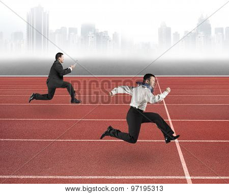 Two Businessmen Running On Red Track