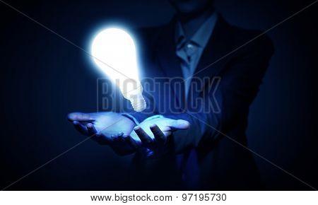 Human hand presenting light bulb concept on palm