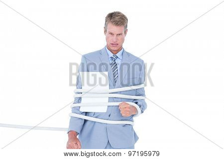 Serious businessman tied up at work on white background